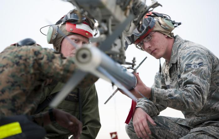 An Airman works alongside Marines to assist with loading munitions. Photo Credit: US Air Force/Senior Airman Armando A. Schwier-Morales.