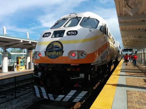 A SunRail train waits at the Sand Lake Rd station. Photo Credit: HARTride 2012.